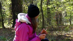 A Young Woman Knocking Nuts Attracting a Hiding and Running Squirrel in Forest. Stock Footage