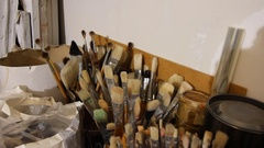 Art studio. Oil painting material. Large and small brushes in beautiful vase and Stock Footage