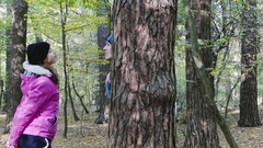 A Young Woman Bowing to a Tree and Kissing a Young Man Hiding Behind a Tree. Stock Footage