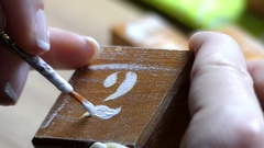 A Girl`s Hand Paints White Number 2 With a Flat Tip Paintbrush Stock Footage