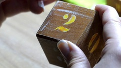 A Woman`s Hand Paints Number 2 on a Wooden Cube With a Flat Tip Paintbrush Stock Footage