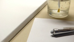 A Hand Cleaning a Flat Tip Paintbrush in a Glass of Water With a White Sheet of Stock Footage