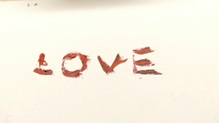 A Hand Painting Out the Word 'love' Using Red Brown Color Stock Footage