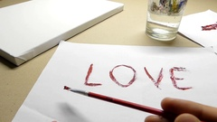 A Hand Painting 'love' and a Line Under it on a Sheet of Paper Stock Footage