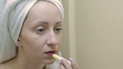 Young beautiful woman applying lipstick on her lips Stock Footage