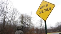 Teenager walks by a Watch Children sign in nature park Stock Footage