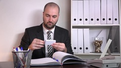 Young businessman modern interior office talking on telephone business card read Stock Footage