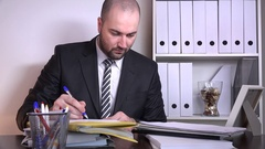 Overworked serious business man working lost under paperwork sigh sighing sad 4K Stock Footage