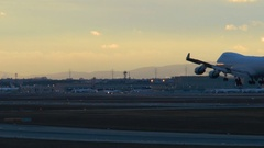 An airplane is landing on runway at dusk Stock Footage