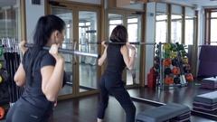 Two women raising bar on shoulders inside sport gym Stock Footage