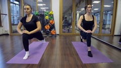 In gym two young women sitting down on a forward split on mats Stock Footage
