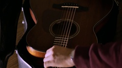 The man pulls out a guitar out of the case Stock Footage