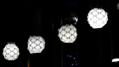 Four White Round Ceiling Plafonds With Curvy Surface Hanging in a Shop at Night Stock Footage