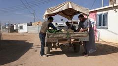 Syrian refugees buy vegetables, donkey cart inside the Zaatari camp in Jordan Stock Footage