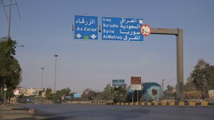 Traffic drives past exit to highway with Syria, Iraq, and Saudi Arabia Stock Footage