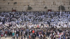 Israeli national flag, crowds of religious people pray at Western Wall Jerusalem Stock Footage