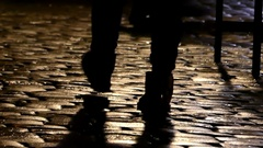 Feet of Several People Walking Along a Cobblestone Sideway at Night in Slo-Mo Stock Footage