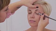 Professional make-up artist applying cream base eyeshadow primer to model eye Stock Footage