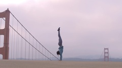 Acrobatic ethnic woman balances on her hands by the Golden Gate Bridge Stock Footage