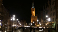 A Polish City Square With a High Old Tower at Night and People Walking Along Stock Footage