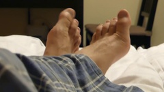 Big Fingers of Man's Lags Moving in Different Direction Laying on the Bad. Stock Footage
