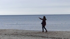 A Loose Haired Girl ia Taking a Selfie While Walking Along a Sandy Seabeach Stock Footage