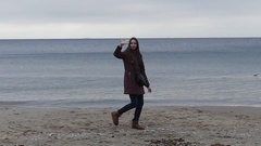 A Smiling Brown Haired Girl is Walking Along a Sandy Sea Beach and Taking a Stock Footage