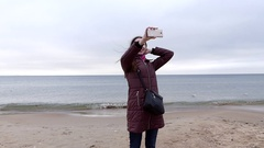 A Nice Girl is Taking a Selfie While Turning Around on a Sandy Seabeach in Stock Footage