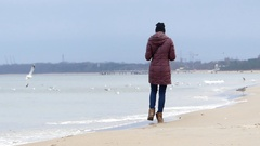 A Young Woman in Black Hat and Brown Anorak Walking Along a Sandy Seabeach in Stock Footage