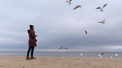 A Young Girl in a Black Hat and a Brown Anorak Throws Bread to Flying Seagulls Stock Footage