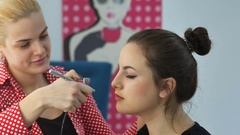 Master making make-up with aerograph for a young girl in a beauty salon Stock Footage