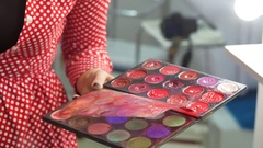 Woman uses shadow palette for applying makeup Stock Footage