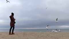A Young Girl in Black Hat and Brown Anorak is Feeding Seagulls on a Sandy Stock Footage