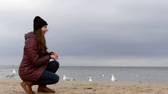 A Young Smiling Girl Sitting and Feeding Seagulls on a Sandy Beach in Autumn in Stock Footage