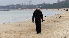 A Young Man Walking Along a Sandy Coastline With a Flock of Seagulls Nearby in Stock Footage