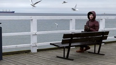A Beautiful Girl Sitting on a Sea Pier Bench and Smiling With a Cup of Coffee Stock Footage
