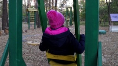 A Woman in a Black Parka and Pink Knitted Hat Sits on a Moving Wooden Swing on Stock Footage