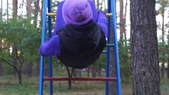 A Smiling Young Woman Hangs on Knees Being on a Playground Ladder and Doing Stock Footage