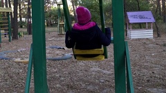 A Woman in Pink Had and Black Parka Sits on a Wooden Swing and Entertaining Stock Footage