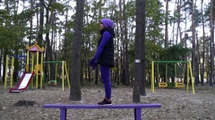 A Young Woman Doing Yoga Squattting Exercise While Standing on a Bench on a Stock Footage