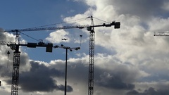 Two Huge Tower Cranes With a Flying Airplane and Birds Against the Beautiful Stock Footage