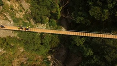 Aerial vertical. Hikers cross a small bridge over a ravine. About adventure, hik Stock Footage
