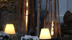 Modern Torcheres With Fire in Tubes Standing in a Windowshop in Snowy Weather Stock Footage