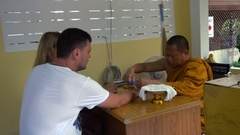 Buddhist Monk ties up Blessed Threads on Tourist Wrists Stock Footage