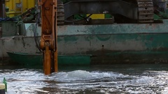 A Huge Excavator Scoop Moves Down in Water With a Lot of Bubbles in Autumn Stock Footage