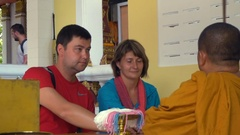 Caucasian tourists get Blessing from Buddhist Monk Stock Footage