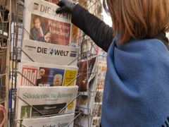 Woman purchases a Die Zeit German newspaper from a newsstand Stock Footage