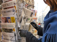 Woman purchases a New York Times with Obama and Trump newspaper from a newsstand Stock Footage