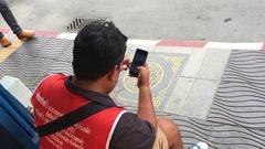 Phuket, Thailand - Elderly thai man surfing instagram photos on a Stock Footage