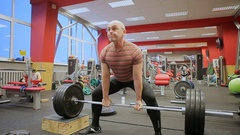 A male muscular athlete performing pull ups with heavy weights on his feet Stock Footage